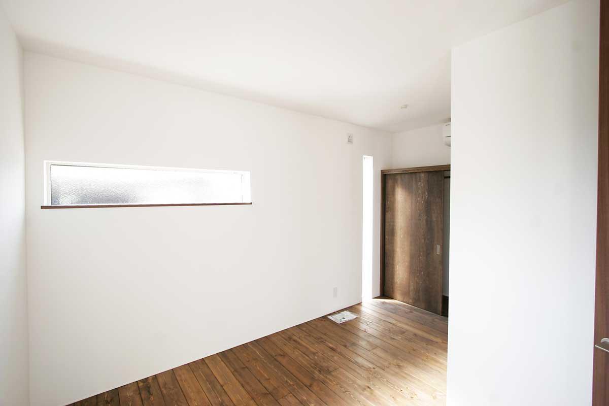 ダークな木材と擦りガラスのスリット窓が個性的な寝室