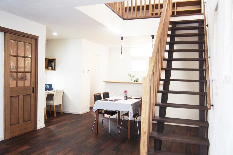 吹き抜け天井に伸びるダークな天然木の階段1