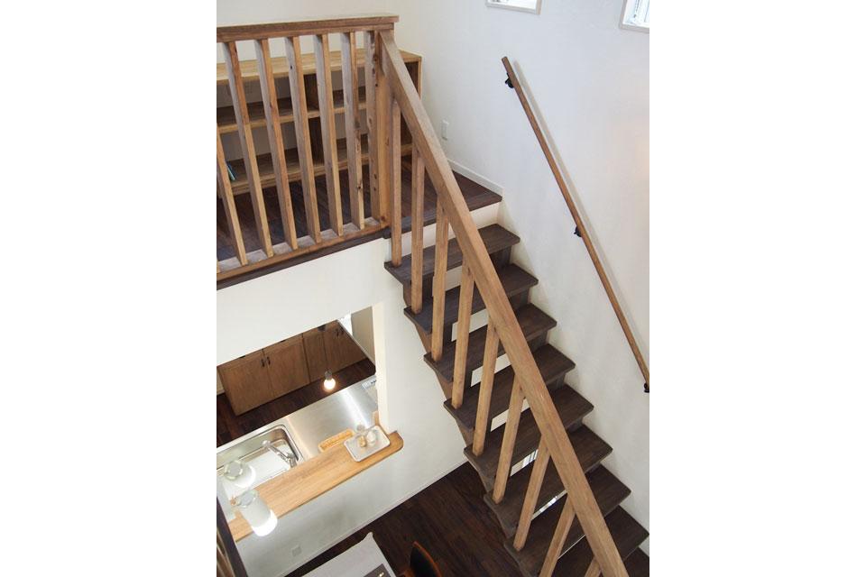 吹き抜け天井に伸びるダークな天然木の階段2