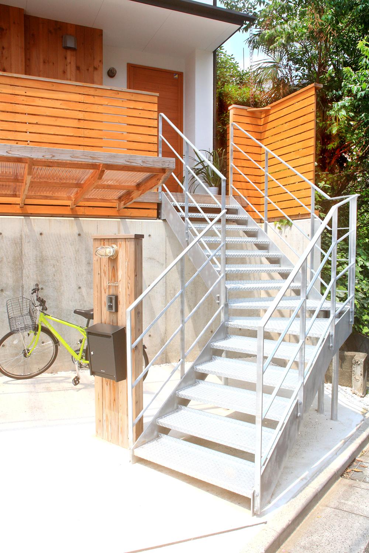 無骨な鉄骨の階段を上がって玄関までアプローチ